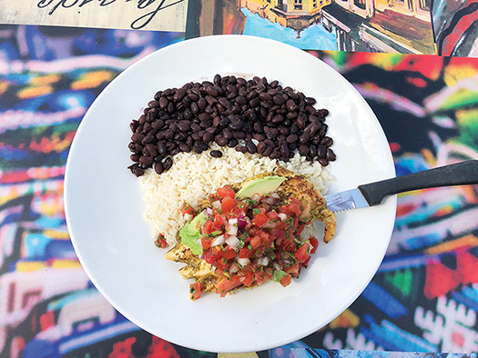 Cilantro Lime Chicken with rice and black beans on a white plate.